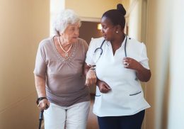 nurse and senior woman having a conversation while walking at the hallway
