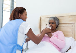 caregiver giving a glass of water to sick senior woman