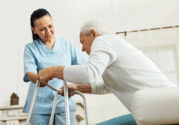 caregiver assisting senior man to get up on the walker