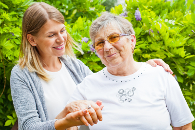caregiver and senior woman are smiling at outdoor
