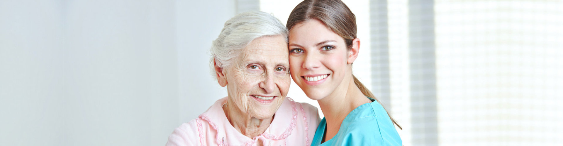 nurse and senior woman are smiling at home
